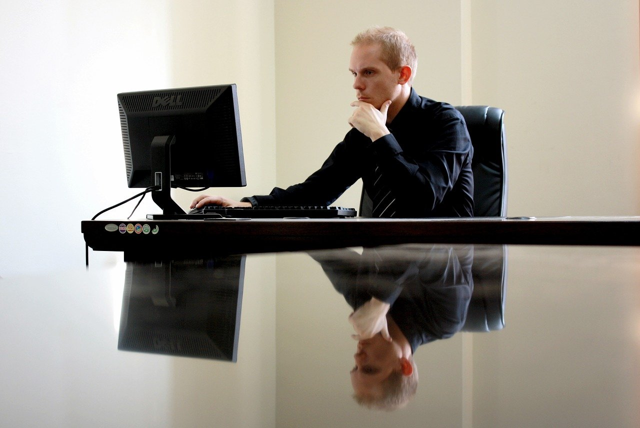 A businessman doing research on his laptop on how to get a real estate license in multiple states.