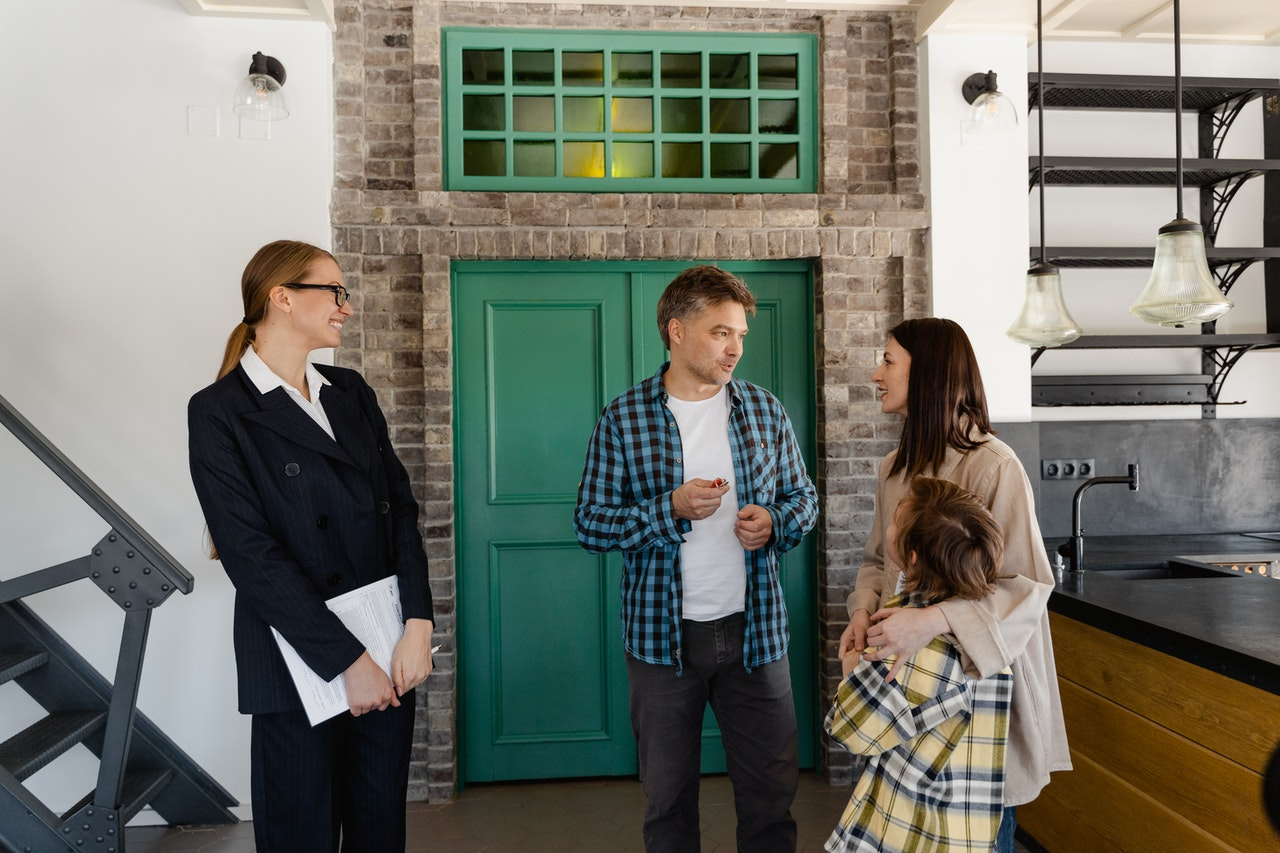 A real estate agent showing a property to a family.
