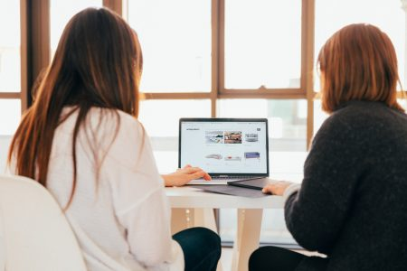 Two women in front of a laptop talking about features of a successful real estate website.
